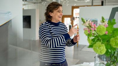 Silvia Modig står i ett konstgalleri och håller skrattande i en pensel. Till höger syns en oskarp blombukett i en vas.