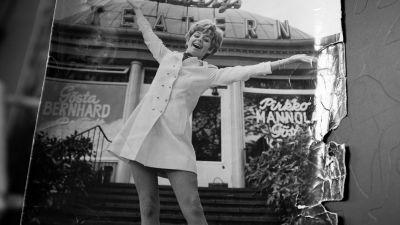 """Ett svarvitt fotografi på Pirkko Mannola där hon står på trappan till Lisebergs Teatern. Hon breder ut armarna mot himlen och ler stort in i kameran. På fönstret till teatern står det stort """"Gösta Bernhard"""" och """"Pirkko Mannola""""."""