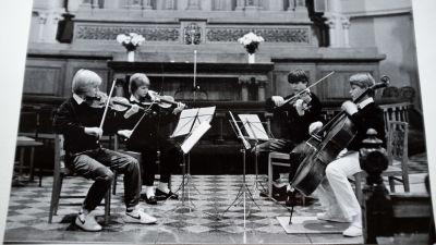 Ett svartvitt foto på en kvartett med fyra pojkar sitter på varsin stol och spelar violin.