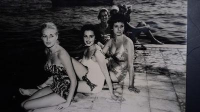 Ett svartvitt fotografi taget på en brygga. Fyra kvinnor i baddräkter sitter på kanten vända mot kameran, varav Pirkko Mannola är andra från vänster.
