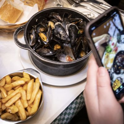 A client taking a snap shot of the the served Mussels and fries