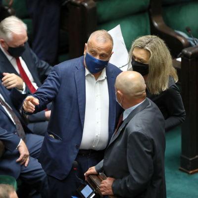 Parlamentariker med munskydd står och diskuterar.