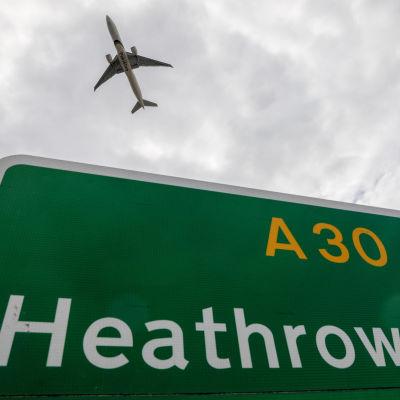 Kyltti, jossa lukee lentokentän nimi. Taivaalla lentävä lentokone.