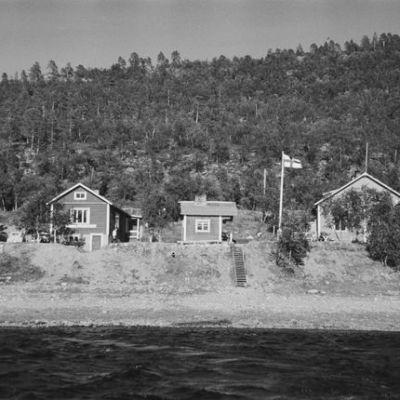 taloja joen rannalla, suomen lippu