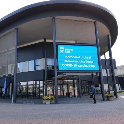 En blå lysande skylt berättar att du ska gå in här för coronavaccinering i Åbo mässcentrum.