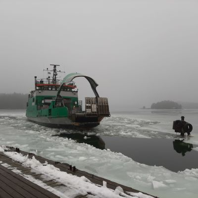 Det gröna förbindelsefartyget Merituuli kommer till Själö med bogporten öppen i ett vintrigt, isigt landskap.
