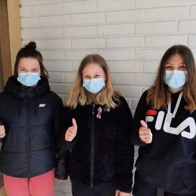 Matilda Tulla, Elsa Kottonen och Kiia Nurmi, tre flickor med munskydd visar tummen upp