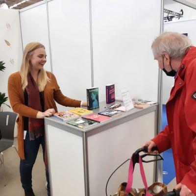 Lotta Westerlund, en dam med ljust lång hår, står vi en montor på bokmässan och diskuterar böcker med en man i röd jacka.