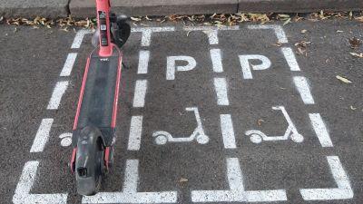 En orange elsparkcykel är parkerad i en ruta på gatan enkom för elsparkcyklar.
