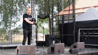En ung man riggar teknik på en scen.
