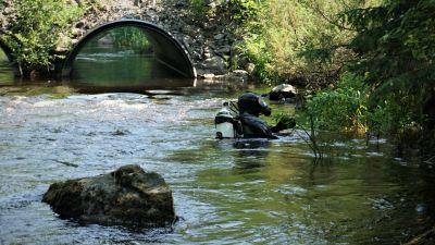 Man i dykardräkt står i ett vattendrag.