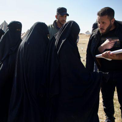 Kvinnor i svarta burkor står i kö och två män talar med dem.