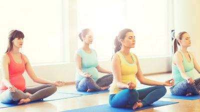 gravida kvinnor på yogalektion