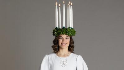 Finlands lucia 2019 Sara Ray iklädd luciakrona med tända ljus och vit särk med rött band.