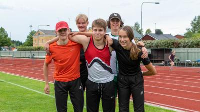 Fem stycken unga idrottare ler mot kameran