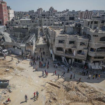 En grupp människor står framför flera sönderbombade byggnader