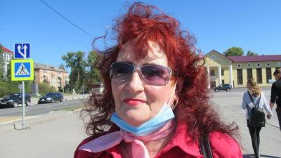 En kvinna med rött hårt och solglasögon ser in i kameran.