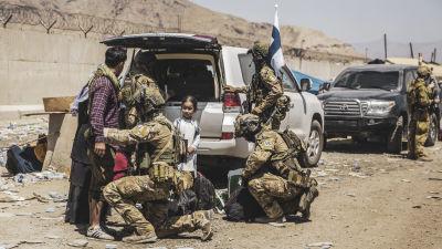 Finländska soldater utför kroppsvisitation vid Kabuls flygplats.