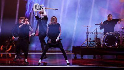 """Blind Channel uppträder på eurovisionsscenen. Gitarristen håller upp baksidan av sin gitarr där det står """"join""""."""