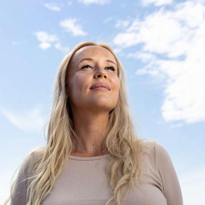 Nainen kuvattuna alakulmasta katsoo ylöspäin, taustalla sinistä taivasta ja pilviä.