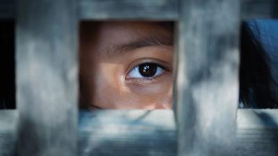 Ett barn tittar ut från bakom ett galler. Endast barnets öga och ögonbryn syns.