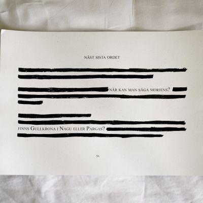 """Ett papper ligger på ett lakan. En del av texten är svärtad oläslig, men det går att tyda texten """"Näst sista ordet, när kan man säga morjens? Finns Gullkrona i Nagu eller Pargas?""""."""