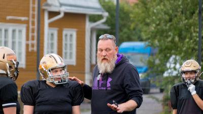 En skäggig man och kvinnor i amerikansk fotboll-spelutrustning är på en gräsplan.