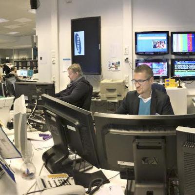 Ylen uutishuone  ja kuvassa toimittajia istumassa työpisteissään