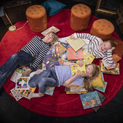 Tre barn ligger på en röd matta bland böcker.