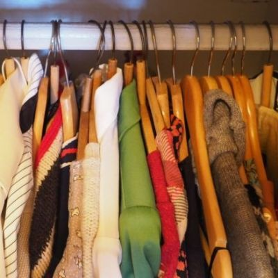 Vaatteita roikkuu vaatetangolla.