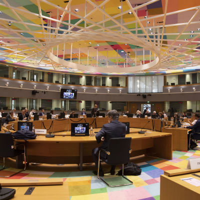 Joukko ihmisiä istumassa suuren pöydän ympärillä. Näkyvillä ruutuja, joissa näkyy kokoukseen osallistuvia.