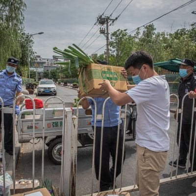 Mies nosti eristysaidan ylitse ruokaa vartijoille ja poliiseille eteenpäin toimitettavaksi keskiviikkona Pekingissä, lähellä suljettua Xinfadin tukkutoria.