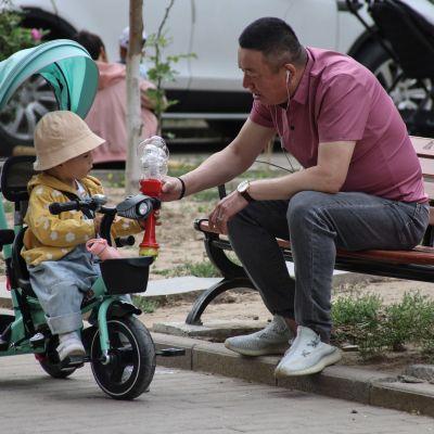 Mies leikki lapsen kanssa Pekingissä toukokuun alussa.