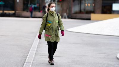 En kvinna med ansiktsskydd på går ute på stan.