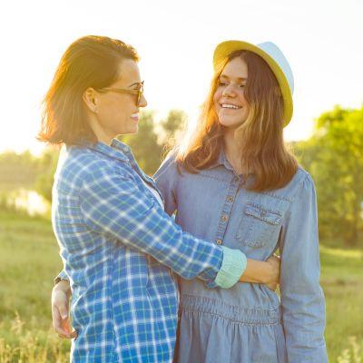 Mamma och dotter står på äng och håller om varandra och skrattar