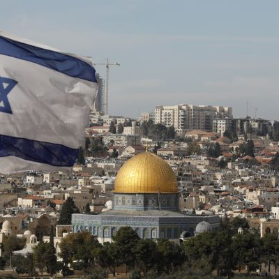 En vy över Jerusalem med Israels flagg i förgrunden.