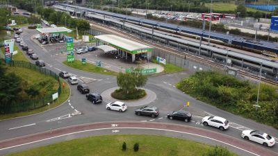 Flybild på en lång bilkö till en bensinstation.