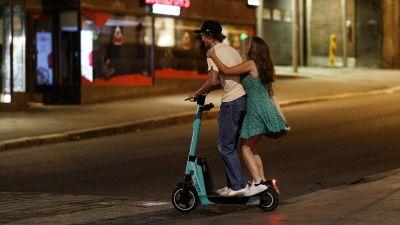 Två personer åker på en elsparkcykel på natten.
