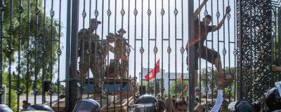 Protester utanför parlamentsbyggnaden i Tunis. Någon försöker klättra över ett högt staket.