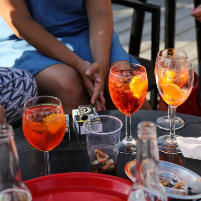 Drycker på ett bord på en uteservering. På bordet syns också tobakspaket.
