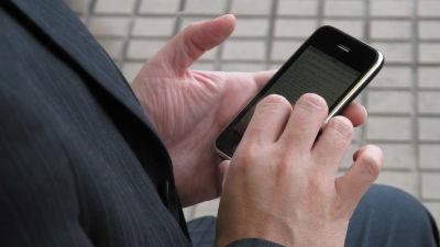 En anonym man som håller en mobil i händerna