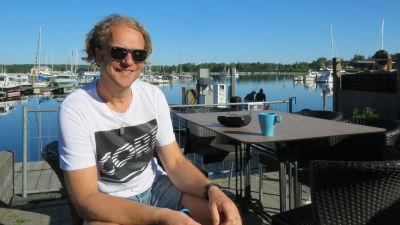 En man med blont lockigt hår, solglasögon, t-skjorta och shorts sitter på en uteservering vid en hamn. (Ekenäs gästhamn)