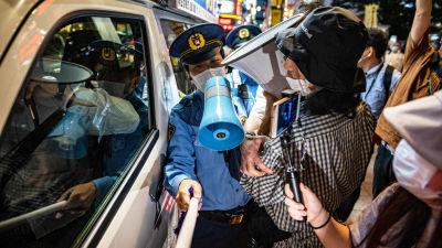 Poliiseja ja mielenosoittajia Tokiossa.