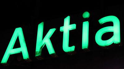 Aktias gröna bokstäver på svart bakgrund.