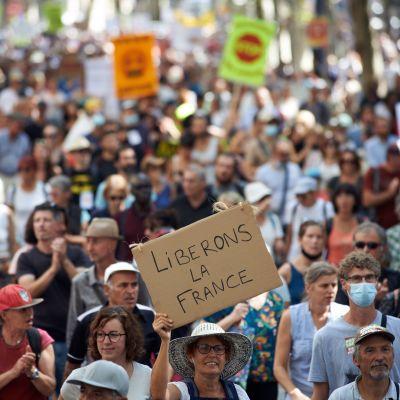 """Människor demonstrerar mot coronadirektiv i Frankrike. En person håller upp en skylt med texten """"Frihet åt Frankrike""""."""