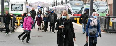 Människor i munskydd på Helsingfors tågstation. I bakgrunden syns tåg.