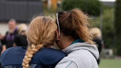 Ryggen och bakhuvudet av två kvinnor som kramas, i bakgrunden idrottsplan.