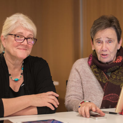 Solveig Nylund och Benita Björklund sitter framför en pekplatta och tittar mot kameran.