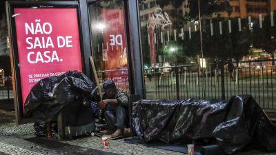 """En hemlös man sover vid en busshållptas intill en skylt med texten """"Gå inte ut från ditt hem"""""""