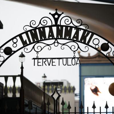 """En skylt som det står """"Linnanmäki"""" på. I bakgrunden ser man några byggnader."""